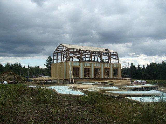 Une maison en construction sur un vaste terrain verdoyant.