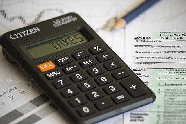 Calculettes affichant TAXES posée sur des feuilles d'impôts.