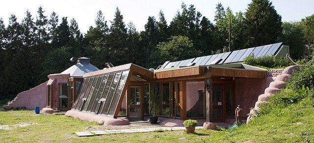 Maison avec panneaux photovoltaïques et baies vitrées.