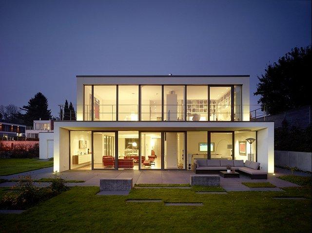 Maison moderne à toiture plate et multiples baies vitrées.