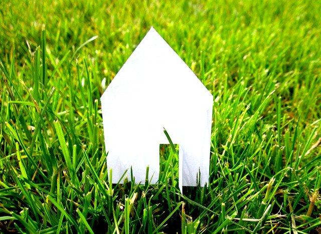 Maison en papier posée sur un gazon verdoyant.