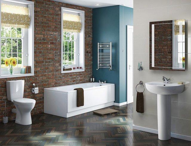 Salle de bain lumineuse avec baignoire, lavabo et toilettes.