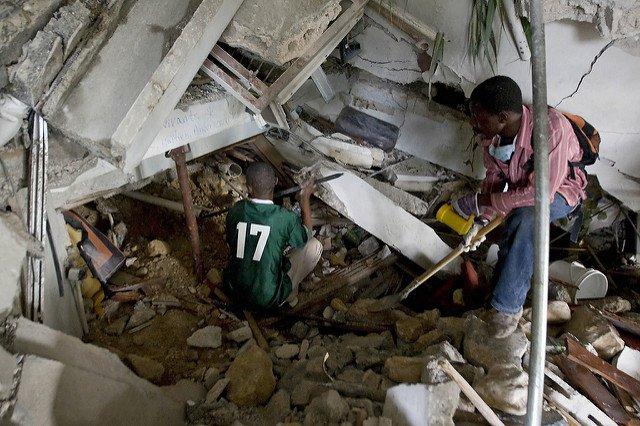 Deux hommes fouillent dans des décombres d'habitations.