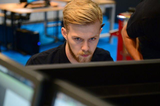 Photographie d'un étudiant en architecture sur un poste informatique.
