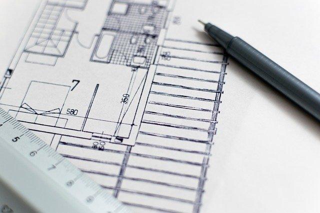 Plan de construction d'un bâtiment avec une règle et un stylo.
