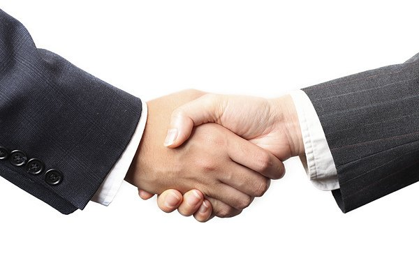 Une main de femme sert celle d'un homme pour conclure un accord.
