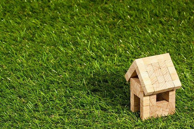 Photographie d'une pelouse avec une petite construction de maison en bois.