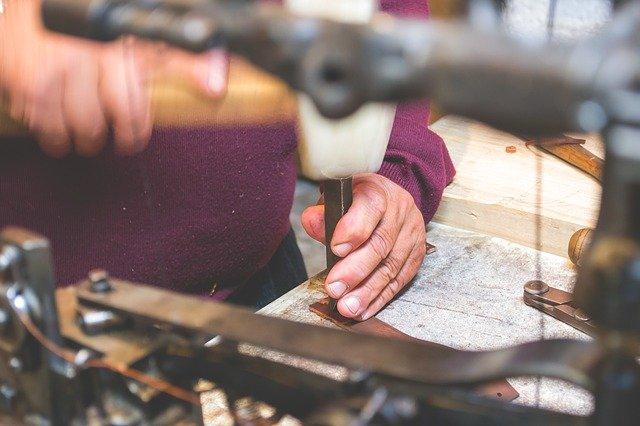 Mains d'un artisan en train de travailler dans son atelier.