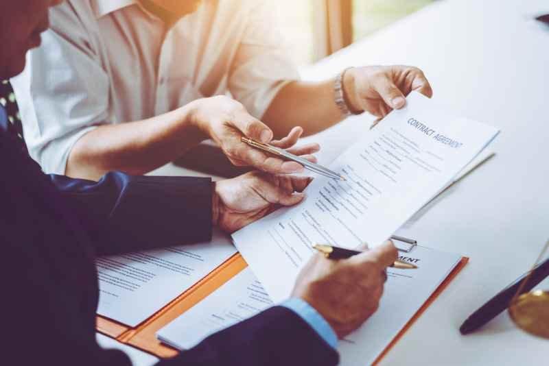 Deux personnes négiciant un contrat d'assurance pour la construction d'une maison.